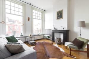 meubelverhuur zwart wit hoog plafond schouw koeienkleed vintage natuurtinten