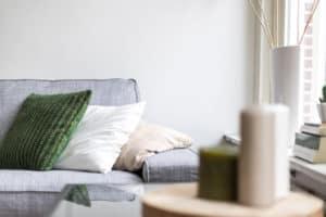 grijze bank kussens accessoires interieur styling groen wit sfeer kaarsen hout natuurtinten meubelverhuur