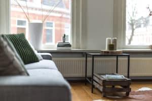 grijze bank wit natuurtinten groen ramen licht woonkamer meubelverhuur